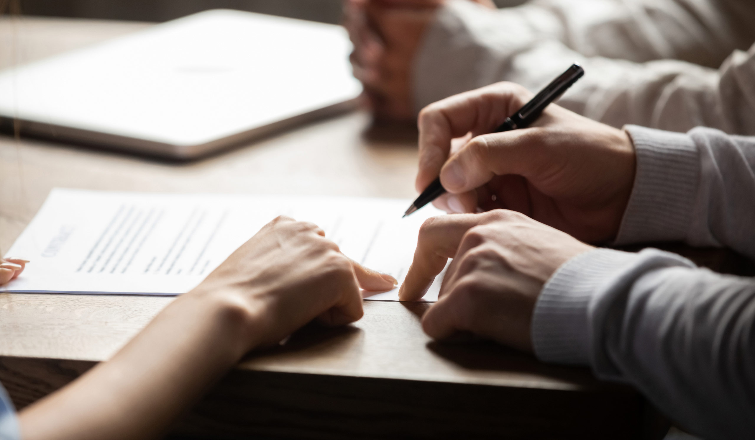 a lawyer and client signing paperwork